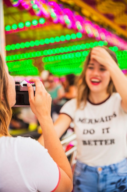 Close-up of young woman taking picture of her friend Free Photo