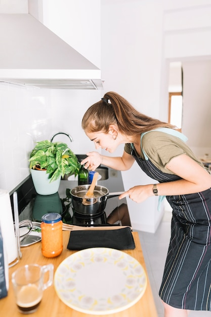 Close-up of young woman tasting soup on sauce pan Free Photo