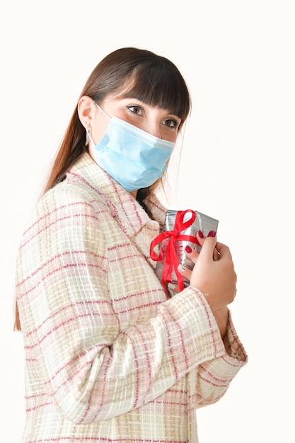 Primo piano di una giovane donna che utilizza una mascherina chirurgica tenendo una confezione regalo vicino al petto su uno sfondo luminoso. Foto Gratuite