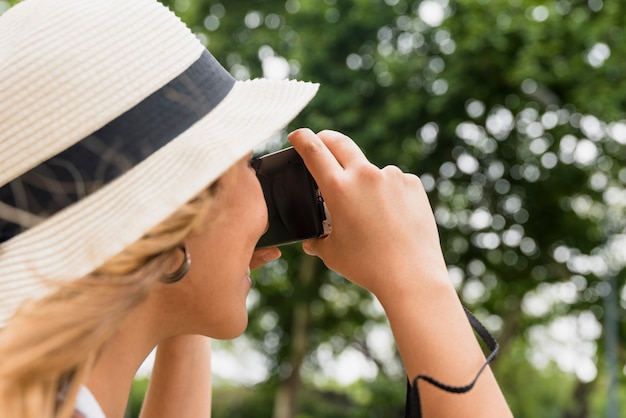 Close-up of young woman wearing hat taking photograph from camera Free Photo