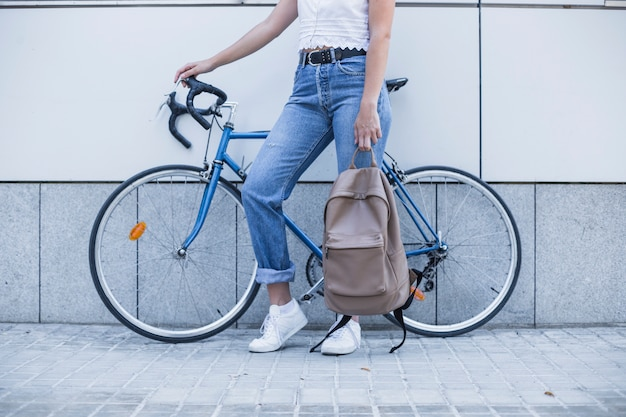 Close-up of young woman with her backpack standing near the bicycle Free Photo