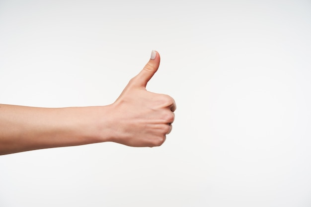 Close up on young woman with white manicure raising hand Free Photo
