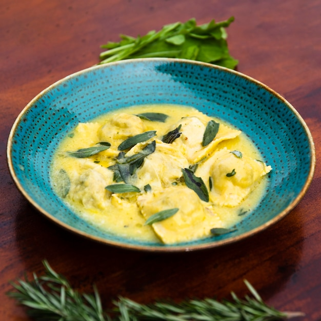 Close-up of yummy ravioli pasta garnish with basil leaf on wooden table Free Photo