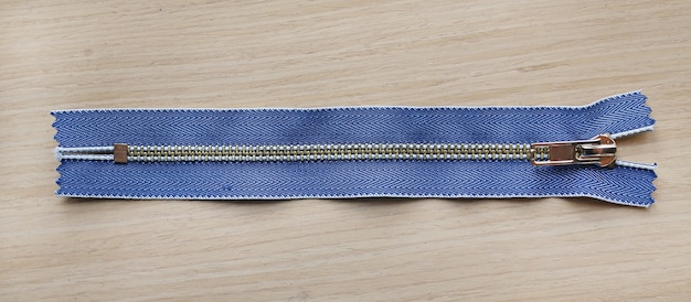 Close-up of zippers on wood table. Premium Photo