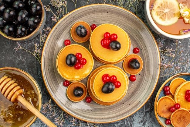 Chiudere la visualizzazione della colazione con la pila di frittelle tazza di tè al limone e miele di amarena Foto Gratuite