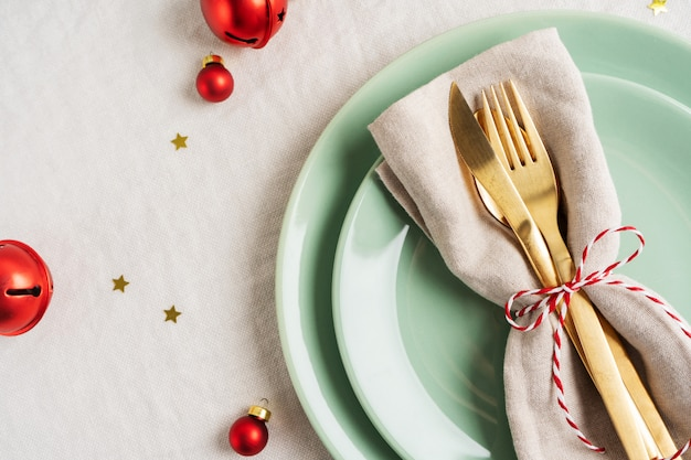 Close view of golden cutlery on light napkin for christmas table setting. Premium Photo