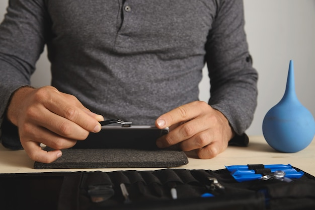 ビューを閉じる、マスターはそれを分解しながらスマートフォンからsimカードスロットを削除するためにピンチャーツールを使用しています 無料写真