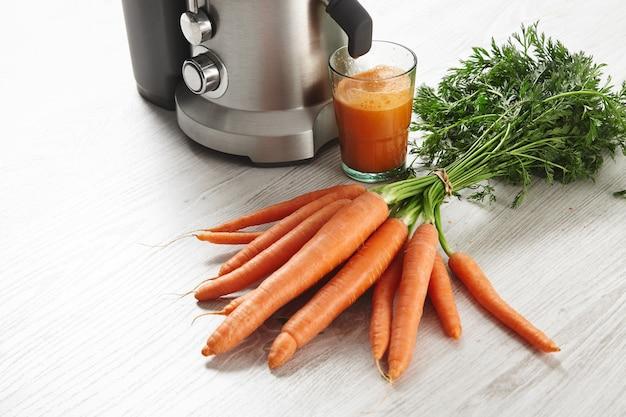 Закройте представление металлическая профессиональная соковыжималка со стеклом, наполненным вкусным соком на завтрак из органической фермерской моркови, лежащей на деревянном столе. Бесплатные Фотографии