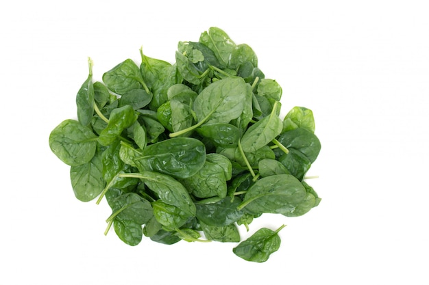 Close view of a pile of fresh spinach, isolated on a white background. Premium Photo