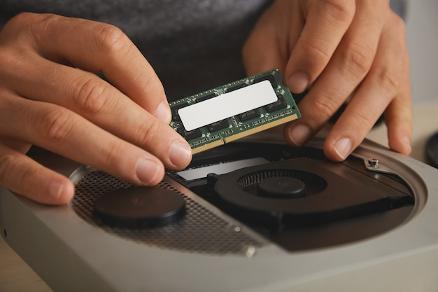 Close view on professional hands removing memory plate to upgrade small personal computer Free Photo