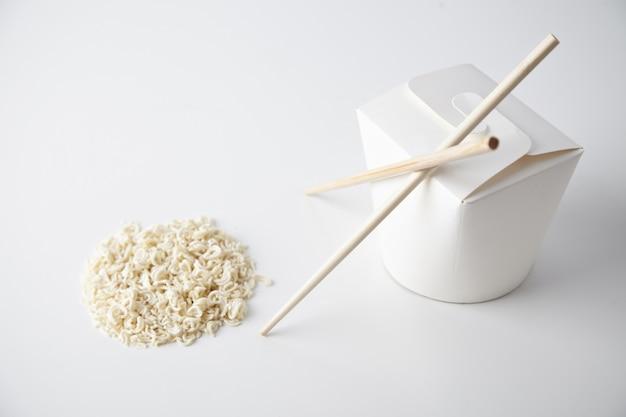 白いクローズフォーカスの商業プレゼンテーションで分離された円形の乾燥パスタの近くに箸が付いている閉じた空白の持ち帰り用麺箱 無料写真