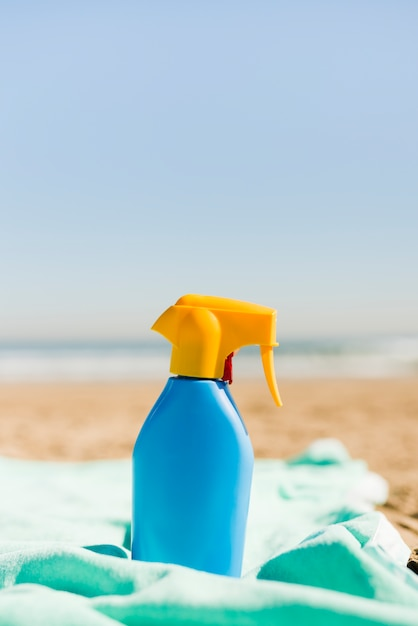 Closed blue sunscreen cosmetics container on turquoise blanket at beach Free Photo