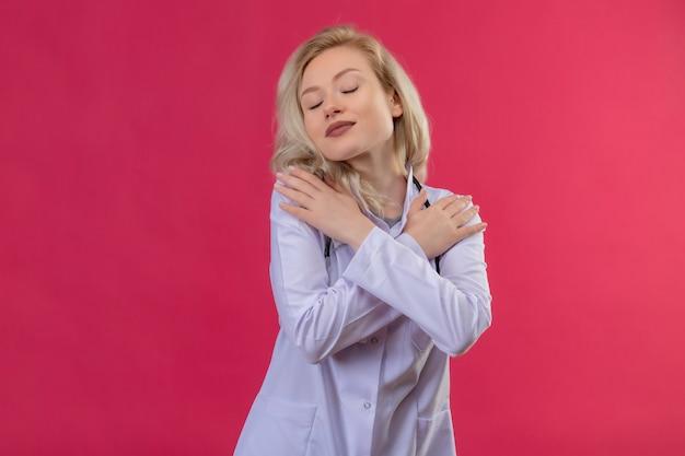 医療用ガウンで聴診器を身に着けている目を閉じた若い医者は、孤立した赤い背景に彼女の手を肩に置きました 無料写真