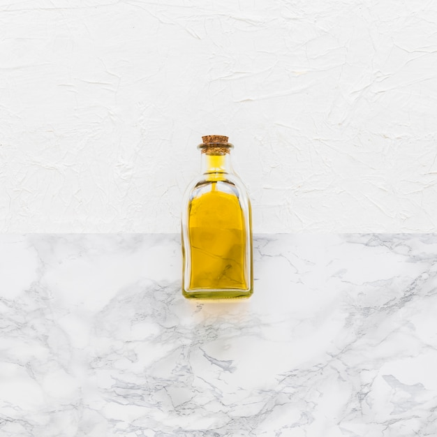 Closed glass oil bottle on two textured backdrop Free Photo
