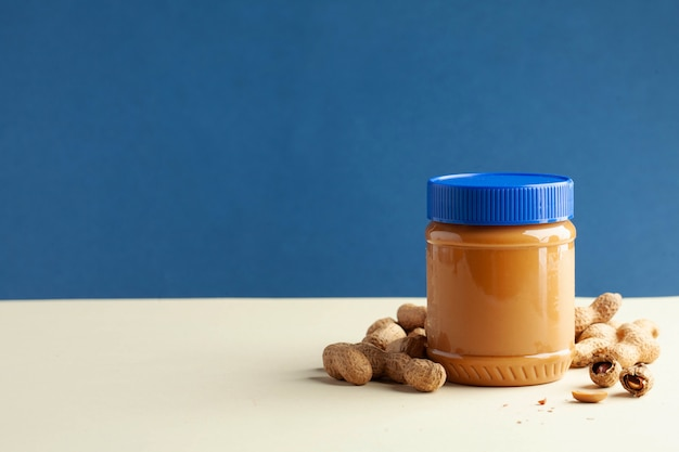 Closed jar of peanut butter, peanuts in their shells. Premium Photo