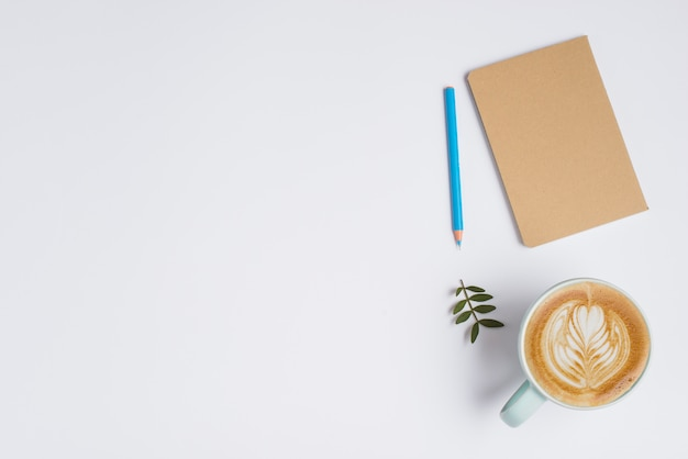 Closed notebook; colored pencil; leaves and cup of coffee with latte art on white background Free Photo