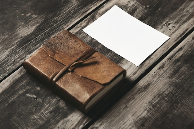 黒い農場のビンテージブラシをかけられた木製のテーブルの上の白い紙のシートの近くのgeniune革カバーの閉じたノートブック 無料写真
