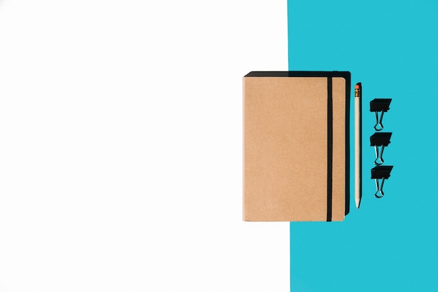 Closed notebook with brown cover; pencil and bulldog clips on white and blue background Free Photo