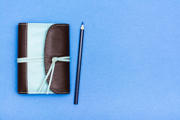 Closed organizer in a two-color leather binding and a pencil on a blue background Premium Photo