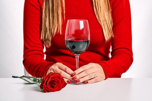빨간 스웨터, 장미와 흰색 배경에 고립 된 와인 잔에 여자의 닫힌 된 계획. C 부부와 데이트의 개념. 프리미엄 사진