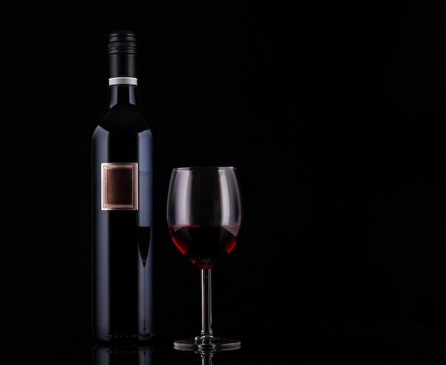 Closed red wine bottle with empty label and glass of wine on black background with reflections Premium Photo