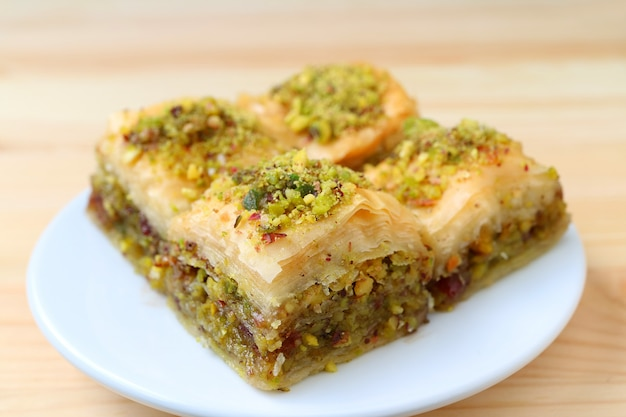 Closed up of baklava with pistachio nuts served on white plate, blurred background Premium Photo