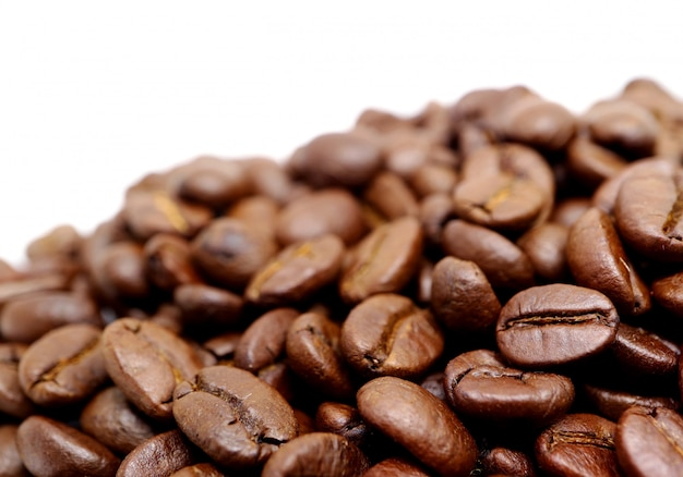 Closed up pile of roasted coffee beans isolated on white background Premium Photo