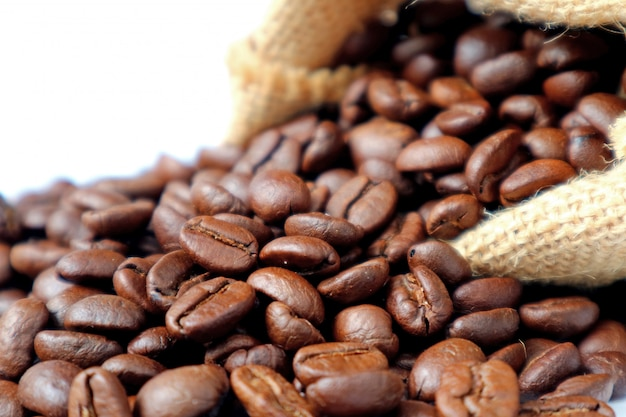 Closed up roasted coffee beans scattered from burlap sack on white background Premium Photo