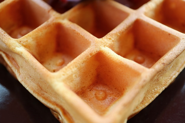 Closed up the texture of a tasty square shaped waffle on a black plate Premium Photo