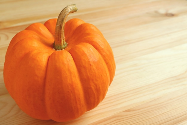 Closed up vivid orange color ripe pumpkin with stem on light brown wooden table. Premium Photo