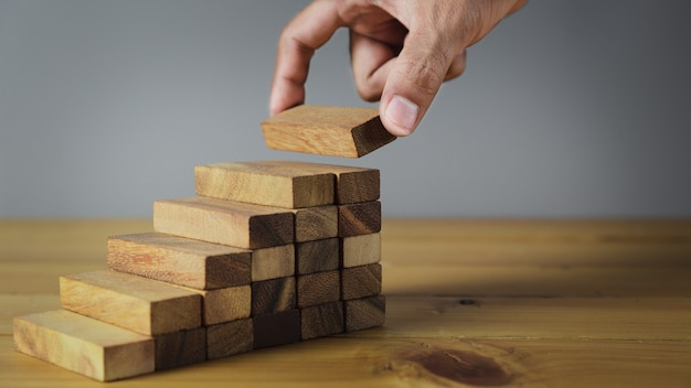 Closer up hands of businessmen,stacking wooden blocks into steps,concept of business growth success - image Premium Photo