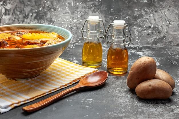 Primo piano e vista laterale della deliziosa zuppa con pollo e patate e cucchiaio sul tavolo scuro e grigio Foto Gratuite