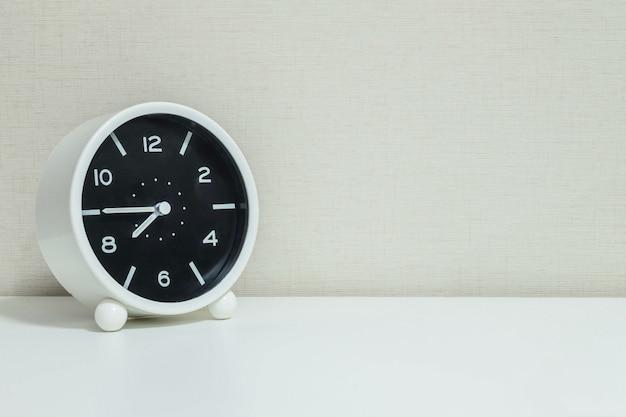 Closeup alarm clock for decorate in a quarter to eight on wood desk Premium Photo