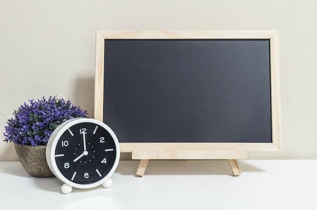 Closeup alarm clock for decorate show 8 o'clock with wood black board on white wood desk Premium Photo