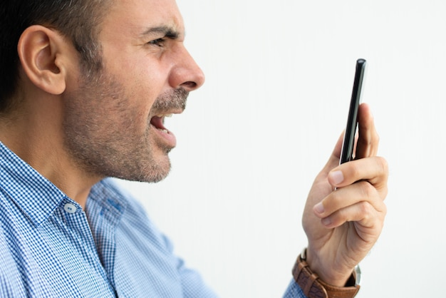 Closeup of angry business man shouting at smartphone Free Photo