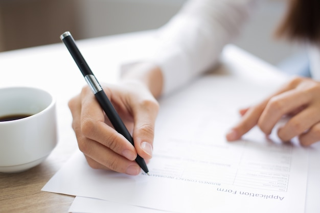 Closeup of applicant completing application form Free Photo