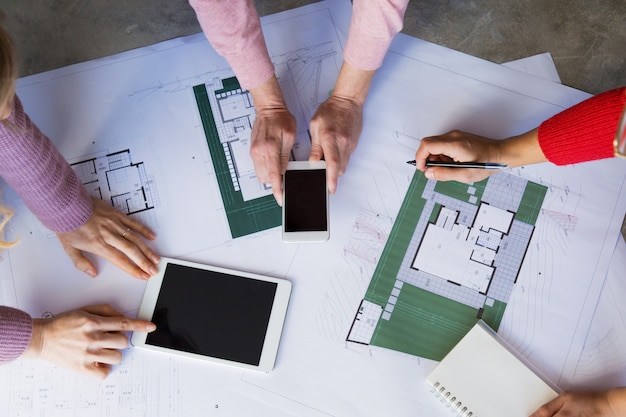 Closeup of architects working with drawings at desk Free Photo