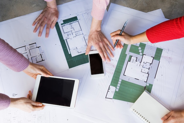 Closeup of architects working with drawings and using gadgets Free Photo