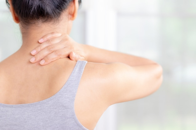Closeup asian woman neck and shoulder pain and injury. health care and medical concept. Premium Photo