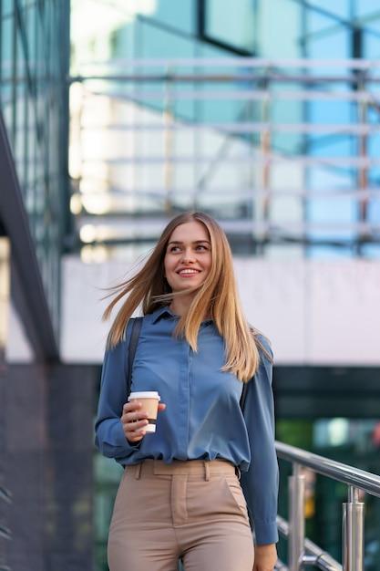 ビジネスビルのテイクアウトコーヒーと動いているクローズアップの魅力的な女性。屋外の温かい飲み物と紙コップを保持している肖像画のブロンドの女の子。 無料写真
