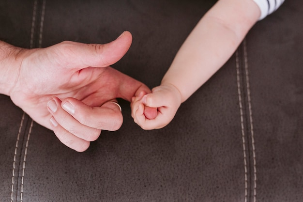 Closeup of a baby holding father's finger at home. family and love concept Premium Photo
