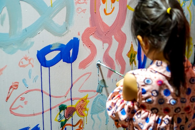 Closeup and back view of asian girl drawing and decorating the walls of her new art classroom Premium Photo