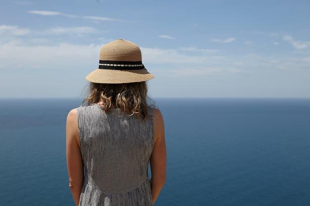 視点で素晴らしい海の景色を楽しんでいるドレスと麦わら帽子の認識できない細いブロンドの女性のクローズアップ背面図。広大な穏やかな海と青い空の美しい景色を眺めるロマンチックな女性 無料写真