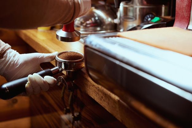 Closeup of barista holding coffee holder with ground coffee near professional coffee machine. Premium Photo