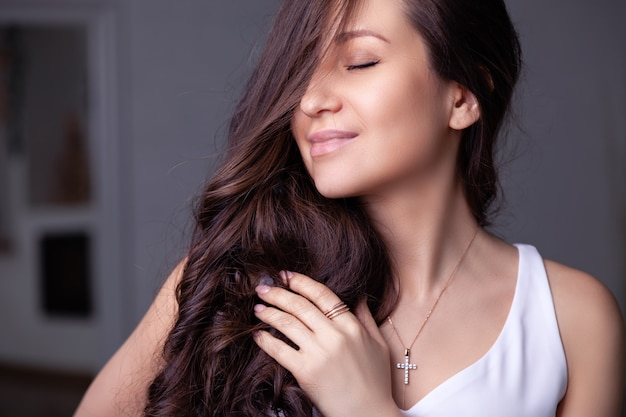 Closeup beautiful brunette girl with long hair in silver jewelry earrings, rings, bracelet, chain, necklace. Premium Photo