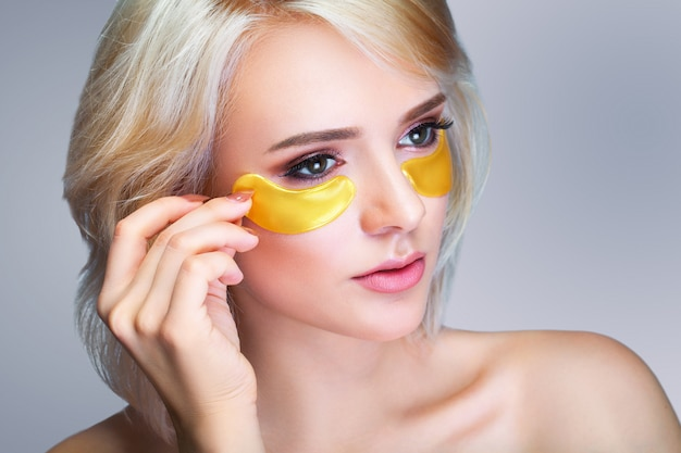 Closeup of beautiful happy smiling woman with moisturizing under eye mask Premium Photo
