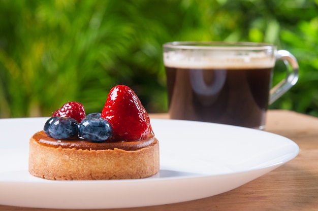 Closeup of beautiful mini tart with berries and cup of coffee Free Photo