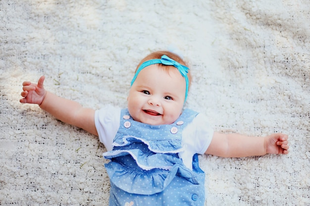 Closeup of beautiful smiling baby with big eyes. happy cute little child having fun in the garden with family. sweet kid Premium Photo