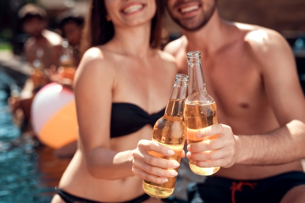 Closeup of beautiful young couple holding bottles of beer Premium Photo