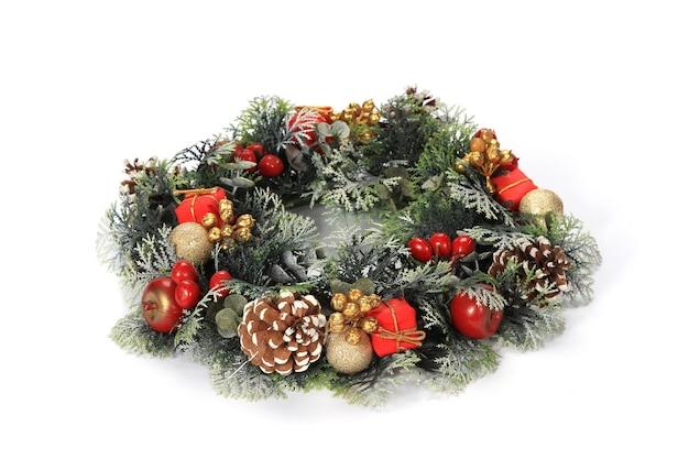 Primo piano di una corona splendidamente decorata con pigne, piccoli regali su uno sfondo bianco Foto Gratuite